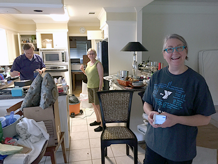 """The Rev. Gena Davis (r) had just put her house on the market when it was flooded. She and husband Gary have spent the past week throwing most of their soaked library onto the curb and taking clothes to the dry cleaners with lots of help from parishioners. """"Well, it's a heck-of-a way to downsize!"""" she said.  Photo/Carol E. Barnwell"""