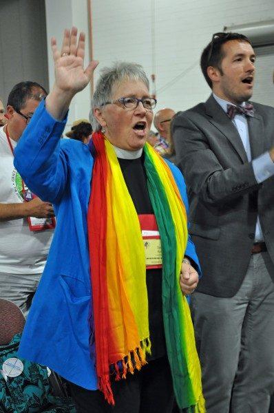 """La Rda. Susan Russell, quien durante mucho tiempo ha abogado por la plena inclusión de los homosexuales en la Iglesia, ex presidente de Integrity y primera asociada de [la iglesia] de la iglesia de Todos los Santos en Pasadena, California, y el Rdo. Michael Sniffen, rector de la iglesia de San Lucas y San Mateo en Brooklyn, Nueva York, capellán de Integrity y quien se define a sí mismo como un """"aliado heterosexual"""", celebran el dictamen del Tribunal Supremo de EE.UU. el 26 de junio en el salón de cultos de la Convención General antes de la eucaristía diaria. Foto de Mary Frances Schjonberg/ENS."""