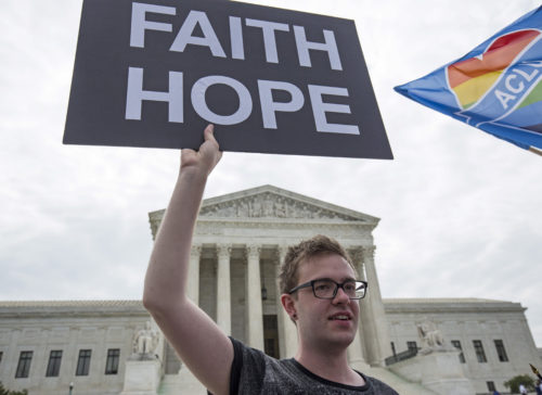 Casey Kend of New York and a supporters of gay marriage holds a sign in front of the Supreme Court in Washington June 26, 2015. A decision in Obergefell v. Hodges, a test of a constitutional right to same-sex marriage, is expected in the coming days.       REUTERS/Joshua Roberts - RTX1HYBK