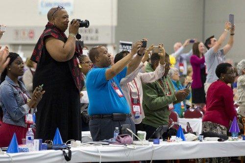 Algunos diputados de pie sobre sus sillas sostienen en alto sus teléfonos, tabletas y cámaras para captar el momento histórico de la entrada del obispo primado electo, Michael Curry, al salón de la Cámara de Diputados. En la foto pueden verse a los diputados Dunstanette Macauley-Dukuly (Newark), la Rda. Sandye Wilson (Newark), Norberto (Bert) Jones (Newark), Delma Maduro (Islas Vírgenes), Wesley S. Williams, Jr. (Islas Vírgenes) y Rosalie Simmonds Ballentine (Islas Vírgenes) Foto de Cynthia L. Black para ENS.