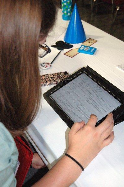 Sarah Neumann, diputada de Massachusetts, estudia el presupuesto por vía de la carpeta virtual en su iPad. Foto de Tracy Sukraw/ENS.