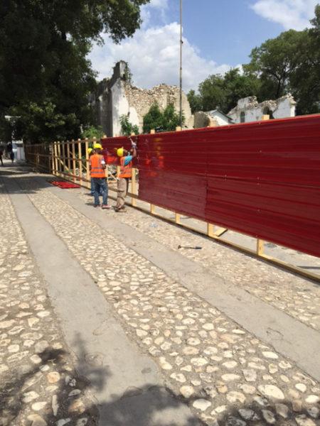 Unos obreros levantan una cerca roja de metal el 20 de julio para proteger el lugar de trabajo. Foto de la Diócesis de Haití.