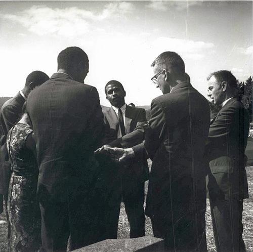 Un grupo se reúne junto a la tumbo de Jonathan Daniels en el cementerio de Monadnock View, en Keene, Nuevo Hampshire. Stokely Carmichael es el segundo de izquierda a derecha, frente a la cámara. Foto de los Archivos de la Iglesia Episcopal.