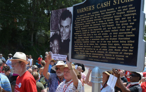 Two friends of slain seminarian Jonathan Daniels hold a photo of him Aug. 15 near the just-dedicated Alabama Historical Marker erected where Varner's Cash Store stood. Daniels was killed outside the building on Aug. 20, 1965, by Lowndes County Special Deputy Thomas Coleman as Daniels saved Ruby Sales from a shotgun blast. Photo: Ellen Hudson/Diocese of Alabama