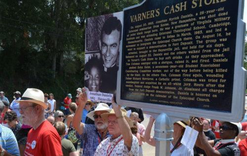 Dos amigos del asesinado seminarista Jonathan Daniels sostienen una foto suya el 15 de agosto junto a la tarja conmemorativa que acababan de dedicar en el lugar donde se encontraba  la tienda [Varner's Cash Store] frente a la cual mataron a Daniels el 20 de agosto de 1965. Foto de Ellen Hudson/Diócesis de Alabama.