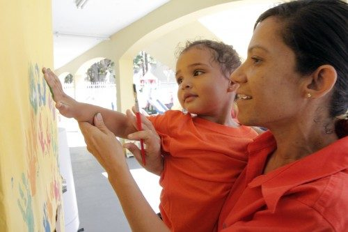 Una maestra ayuda a un niño a hacer una impresión de su mano en verde fuera del aula. Foto de Lynette Wilson/ENS