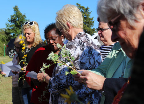 Members of St. Paul's and guests gather at the grave of Mai DeKonza for the blessing and dedication of a stone on her previously unmarked grave, 56 years after her death.
