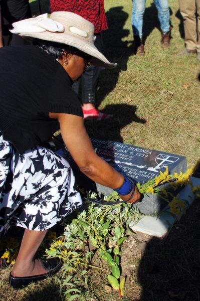 Hazel Washington lays flowers at the grave of Mai DeKonza. Photo: Melodie Woerman/Diocese of Kansas