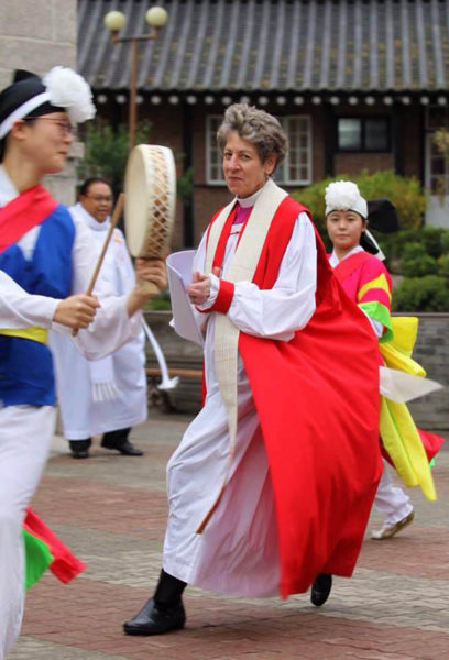 Presiding Bishop Katharine Jefferts Schori dances Oct. 1 with a traditional Korean pungmul group with outside the Anglican Cathedral of St. Mary and St. Nicholas in downtown Seoul before the opening Eucharist of Episcopal Asiamerica Ministries International Consultation. Photo: David Copley