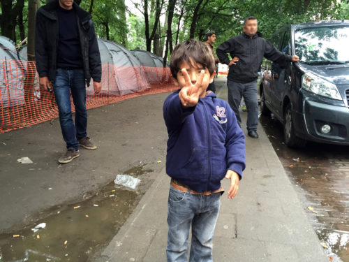 A boy from Iraq offers a peace sign from his temporary home at a refugee camp in Brussels. Photo: Felicity Handford