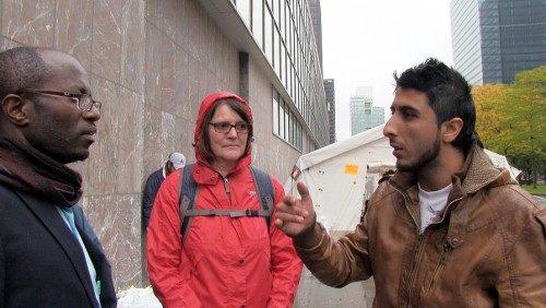 Janvier Nzamutuma (a la izquierda) y Felicity Handford (al centro), feligreses ambos de Todos los Santos, escuchan las inquietudes de un refugiado iraquí respecto al tiempo que lleva procesar a los recién llegados a Bélgica. Foto de Matthew Davies.