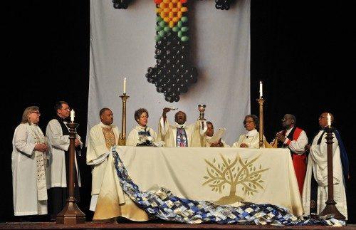 El obispo primado electo Michael B. Curry eleva el pan y el vino durante la vigilia del 31 de octubre ofrecida por la Unión de Episcopales Negros en el Arsenal de Washington, D.C. la víspera de la instalación del 27º. Obispo Presidente y Primado de la Iglesia Episcopal. Junto a él, en el altar, se encuentran, de izquierda a derecha, la Rda. Gay Clark Jennings, presidente de la Cámara de Diputados; el Rdo. Canónigo Michael Buerkel Hunn, a punto de convertirse en canónigo del Obispo Primado para el Ministerio; el Rdo. Guy Leemhuis, diácono de la Diócesis de Los Ángeles que sirvió como capellán de la Obispa Primada durante el oficio; la obispa primada Katharine Jefferts Schori; la Rda. Christine L. McCloud, diácona de la Diócesis de Newark, que sirvió como capellán de Curry durante el oficio; la Rda. Diane Peterson, diácona de la Diócesis de Connecticut, que sirvió como diácono de la misa; el Rvdmo. Nathan Baxter, antiguo obispo de Pensilvania Central y la Rda. Canóniga Sandye Wilson, presidente nacional honoraria de la Unión de Episcopales Negros, que predicó durante el oficio. Foto de Mary Frances Schjonberg/ENS.