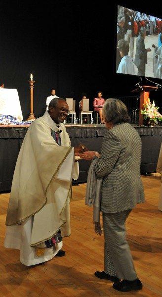 El obispo primado electo Michael B. Curry administra la comunión durante la vigilia del 31 de octubre ofrecida por la Unión de Episcopales Negros en el Arsenal del D.C. la víspera de su instalación como el 27º. Obispo Presidente y Primado de la Iglesia Episcopal. Foto de Mary Frances Schjonberg/ENS.