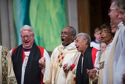 El obispo primado Michael B. Curry, al centro, canta junto a Barbara Harris, obispa sufragánea de Massachusetts (jubilada), la primera obispa en la Comunión Anglicana; Dean Wolfe, obispo de Kansas y vicepresidente de la Cámara de Obispos y otras personas durante el oficio de instalación el 1 de noviembre en la Catedral Nacional de Washington. Foto de Donovan Marks (c) 2015, WNC.