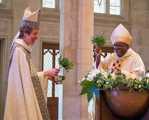 El obispo primado Michael B.Curry y la 26ª. obispa primada Katharine Jefferts Schori intercambian una risa juguetona mientras se preparan para asperjar a la congregación reunida en la Catedral Nacional de Washington para el oficio de instalación de Curry. Foto de Danielle Thomas (c) 2015 WNC.
