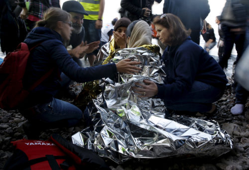 Volunteers try to comfort a pregnant Syrian refugee shortly after arriving by a raft on the Greek island of Lesbos, November 17, 2015. REUTERS/Yannis Behrakis