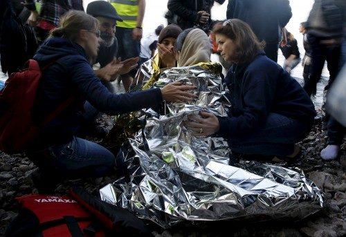 Voluntarias intentan confortar a una siria embarazada poco después de llegar en una balsa a la isla griega de Lesbos el 17 de noviembre. Foto de Yannis Behrakis/Reuters.