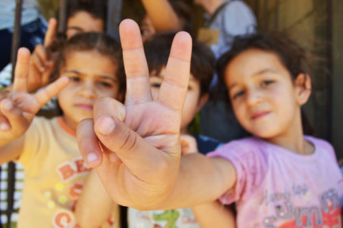 Syrian refugee children at a half-built apartment block near Reyfoun in Lebanon, close to the border with Syria, give the peace sign. The families fled Syria due to the war and are now living on a building site. Photo: Eoghan Rice/Trocaire via Wikimeida