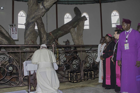 Pope Francis prays at the torture tree at the Anglican Shrine to the Ugandan Martyrs in Namugongo. Photo: Petero Buyondo and Francis Emorut