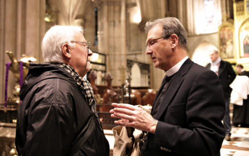 The Rev. Very Mark Richardson, president and dean of the Church Divinity School of the Pacific, right, speaks to a parishioner following a Dec. 6 Eucharist at the Cathedral of the Holy Trinity in Paris. Photo: Jere Skipper