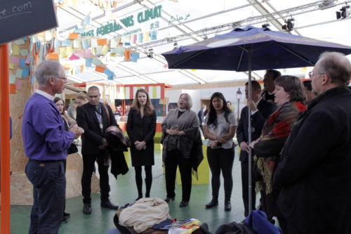 California Bishop Marc Andrus leads Episcopalians and others in a pop-up worship service in the green zone at COP21. Photo: Lynette Wilson/ENS