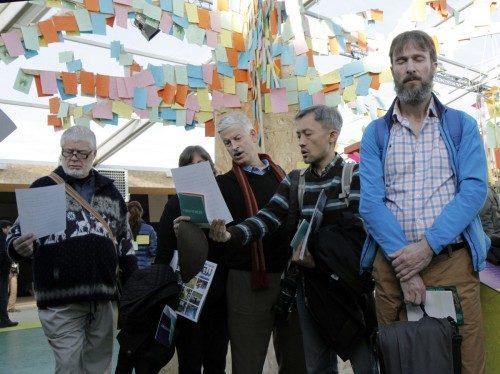 """El culto espontáneo tenía lugar debajo de un """"árbol de mensajes"""" donde las personas dejaban mensajes ambientalistas. El culto incluía oración, meditación, reflexión y cánticos, fundamentalmente de Taizé. Foto de Lynette Wilson/ENS."""