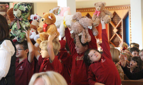 Holy Innocents Episcopal School third-graders Davis Jabaley, Carter Scott, Will Thomas and Mason Core hold up stuffed bears to be blessed. Third-graders at the school bought bears to give to children at Emmaus House , a ministry of the Episcopal Diocese of Atlanta. Photo: Holy Innocents Episcopal School
