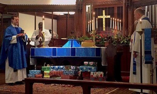 El Rdo. T. Stewart Lucas, a la izquierda, rector de la iglesia episcopal de la Natividad, y el Rdo. David Eisenhuth, pastor del Santo Consolador, una congregación de la Iglesia Evangélica Luterana en América, bendicen el 13 de noviembre paquetes de Navidad para el Centro Internacional de Marinos de Baltimore. Estos serán los únicos regalos que muchos de los marinos que trabajan en barcos atracados temporalmente en el puerto de Baltimore recibirán este año. Las dos congregaciones comparten el espacio de la iglesia de la Natividad así como algunos ministerios, tales como el de las cestas de Navidad para los marineros. Foto de Rob Sohlberg vía Facebook