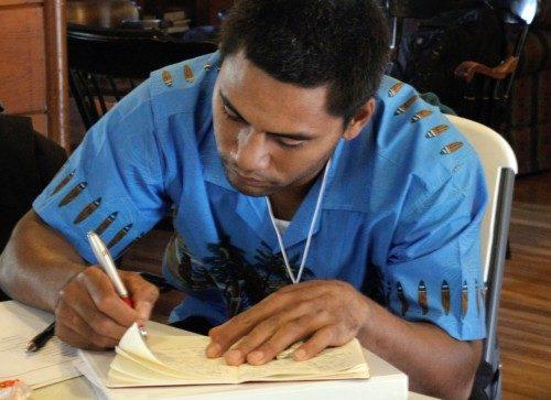 Nicholas Lino, de la Diócesis de Hawái, escribe en su diario durante la peregrinación a Ferguson, del 8 al 12 de octubre, auspiciada por la Sociedad Misionera Nacional y Extranjera. Foto de Lynette Wilson/ENS.