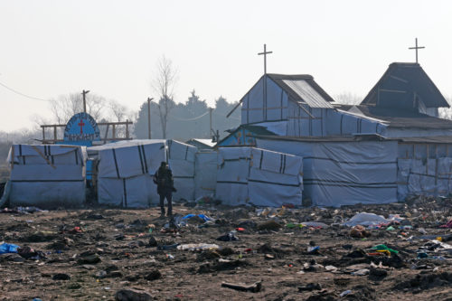 """A refugee walks past the church in the dismantled area of the camp called the """"Jungle"""", in Calais, France, March 14. REUTERS/Pascal Rossignol"""