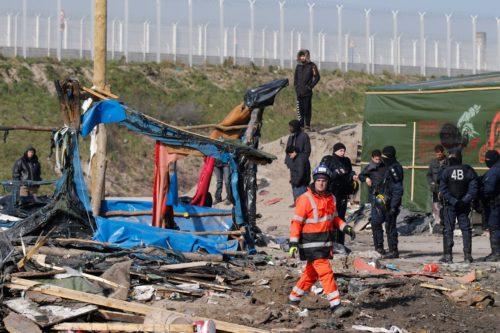 """Trabajadores demuelen improvisados albergues el 14 de marzo mientras los refugiados y la policía antimotines presencian el desmantelamiento parcial del campamento llamado """"La Jungla"""" en Calais, Francia. Foto de Pascal Rossignol/REUTERS."""