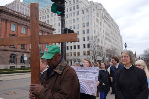 """Robert Yearwood, sexton of Trinity Church, carried the cross through the streets of Boston as area Christians remembered Jesus' suffering with a march through the city on Good Friday 2015. The Rev. Rainey Dankel, also of Trinity, was one of the organizers of the """"Stations of the City."""" Photo: Patricia Hurley"""