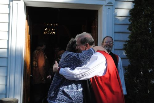 Archbishop Fred Hiltz hugs Canon Ginny Doctor, indigenous ministries coordinator for the Anglican Church of Canada, following the Mohawk Chapel service. National Indigenous Anglican Bishop Mark MacDonald watches over Hiltz's shoulder. Photo: André Forget