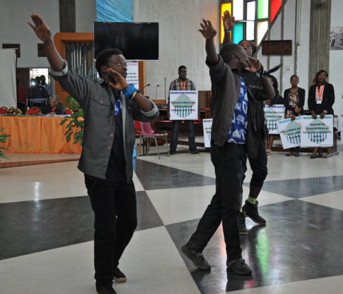 Three young Zambian men dance their faith during a presentation April 16 on local ministry in Lusaka. Photo: Mary Frances Schjonberg/Episcopal News Service