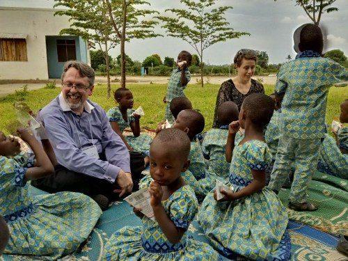 El Rdo. C. K. Robertson, canónigo del obispo primado Michael Curry para el ministerio más allá de la Iglesia Episcopal, y Rebecca Linder Blachly, asesora principal para África del Departamento de Estado de EE.UU. en la Oficina de Religión y Asuntos Globales, juegan con unos huérfanos en el Orfanato Valentine el 2 de abril, durante una visita del grupo a ministerios de asistencia comunitaria de la Diócesis de Da es-Salam, Tanzania. Foto de Andrea Mann.