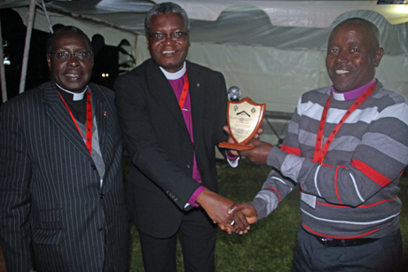 Bishop of Nairobi Joel Waweru receives the Anglican Communion's new youth work recognition award from Bishop James Tengatenga, the chair of the ACC, watched on by Bishop of Lusaka David Njovu. Photo: Gavin Drake/Anglican Communion News Service