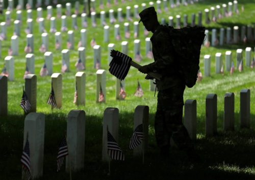 A soldier of the 3rd U.S. Infantry Regiment (The Old Guard) places flags in front of the graves at Arlington National Cemetery in Washington, U.S., May 26. Photo: Joshua Roberts/Reuters