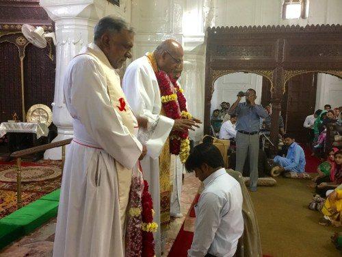 Después del oficio del domingo en la iglesia de Todos los Santos en Peshawar, el Rdo. Canónigo Patrick Augustine impone las manos sobre los miembros de la congregación y ora por su restauración.