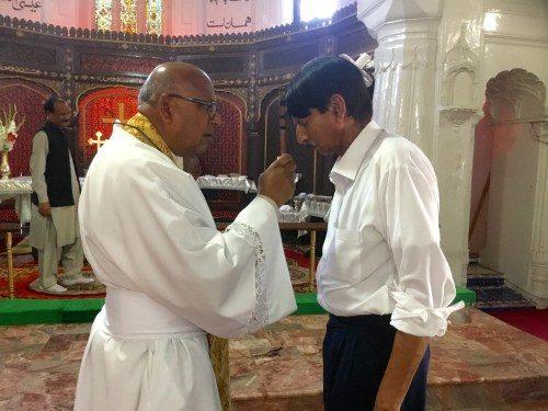 El Rdo. Canónigo Patrick Augustine ora por la curación con el jugador de tablá de la iglesia de Todos los Santos en Peshawar que resultó gravemente herido en el atentado con explosivos que tuvo lugar en la iglesia en 2013.