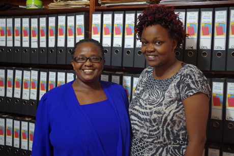 Juliette Mukankwiro and Dinah Igiraneza, part of the Kigali archive team, pose in front of some of the material they have sorted and stored. Photo: Jesse Zink