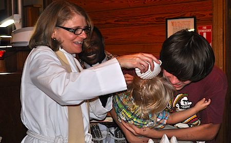 The Rev. Betsy Randall baptizes a baby during a mission trip to All Saints Episcopal Church in rural Atlanta, Texas.