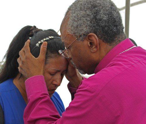 El obispo primado Michael Curry bendice a una mujer que vive en el campamento de refugiados Esteros#2 en Manta, Ecuador. Foto de Edgar Giraldo.