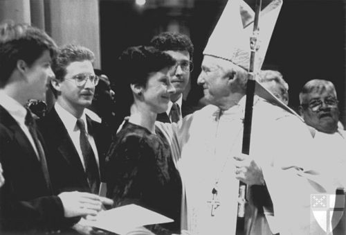 Newly installed Presiding Bishop Edmond L. Browning is congratulated by his wife, Patti. Sons John (far 1.) and Mark look on, as does son Philip (c., partially blocked, between and behind them) during the service at Washington Cathedral. Photo: Episcopal News Service via Episcopal Archives