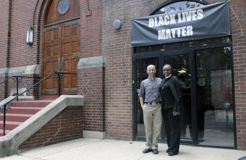 The Rev. Peter Jarrett-Schell, rector, and the Rev. Gayle Fisher-Stewart, associate rector, of Calvary Episcopal Church in Washington, D.C., pose for photo under a Black Lives Matter banner. Photo: Lynette Wilson