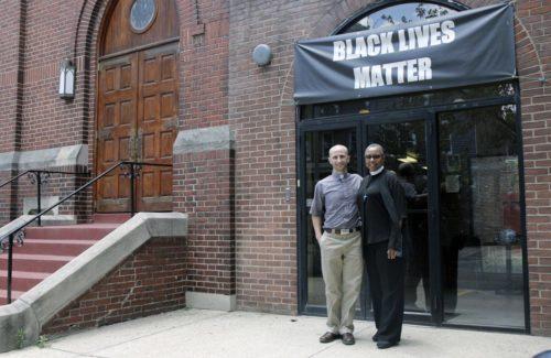 """El Rdo. Peter Jarrett-Schell, rector, y el Rdo. Gayle Fisher-Stewart, rector asociado, de la iglesia episcopal El Calvario en Washington, D.C. posan para una foto debajo de un cartel de la campaña """"La vida de los negros importa"""". Foto de Lynette Wilson."""