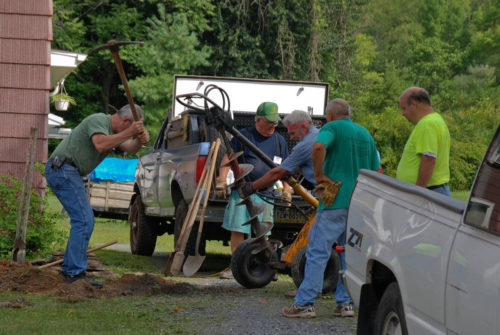 Happy volunteers use a gas auger as they dig footers for a disabled veteran's wheelchair ramp. Photo: Diocese of Central Pennsylvania