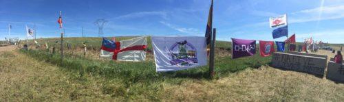 La bandera de la Iglesia Episcopal aparece atada a una cerca en el campamento de protesta del Círculo de Piedras Sagradas, junto con las banderas de otras organizaciones y tribus que participan en la protesta contra el Oleoducto para el Acceso a las Dakotas. Foto de Brandon Mauai vía Facebook.
