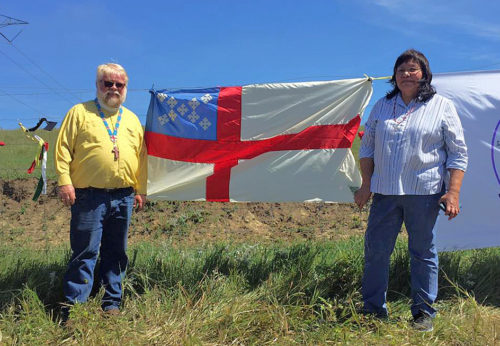 The Rev. John Floberg, who has ministered on the Standing Rock Indian Reservation for 25 years, and Carmine Goodhouse, a member of St. Luke's Episcopal Church in Fort Yates, North Dakota, stand near an Episcopal Church flag that was added to the flags of other organizations and tribes participating in the protest against the Dakota Access Pipeline. Photo: Facebook/John Floberg page.