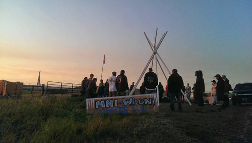 "People protesting the Dakota Access Pipeline that would begin in North Dakota stand at sunset in the Camp of Sacred Stones near a sign reading ""mni wiconi,"" Lakota for ""water is life."" Photo: Indigenous Environmental Network via Facebook"