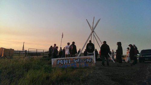 """Manifestantes que protestan por el Oleoducto para el Acceso a las Dakotas, que comenzara en Dakota del Norte, de pie a la puesta del sol en el Campamento de las Piedras Sagradas junto a un cartel en que puede leerse """"mni wiconi"""", que en lengua lakota quiere decir """"el agua es la vida"""". Foto de la Red Medioambiental Indígena vía Facebook."""